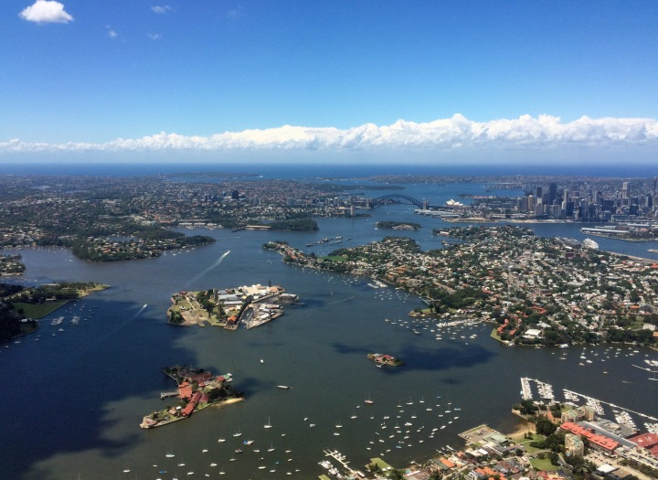 Sydney Harbour, looking east to the Heads. The long boat wakes mark the main flow of the harbour (Parramatta River) from the western suburbs and out under the Bridge. (© airscape Photo)