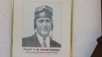 "The portrait of ""Shorty"" Shortbridge, displayed with the collected relics of his lost aircraft. © Ken Watson"