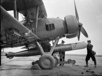 Fitting torpedoes to a Swordfish before a training exercise out of RN station HMS Jackdaw, Crail, Fife. (IWM A3168)
