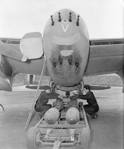 Looking into the fangs of Mosquito FB Mark VI, MM403 'SB-V' of No. 464 Squadron RAAF at RAF Hunsdon in Hertfordshire, as Armourers prepare a load of 500-lb bombs. (IWM CH 12407)
