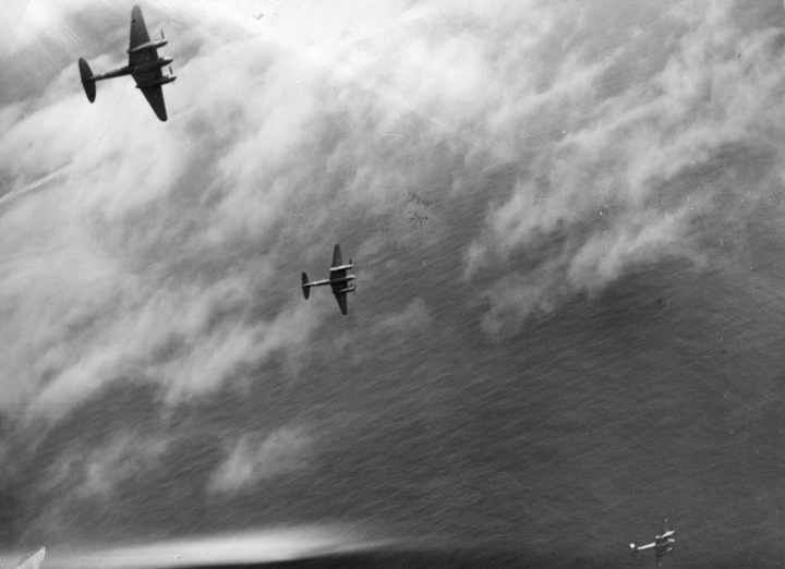 A flight of RAAF Mosquitoes (most likely from Amberley, QLD) peel off and dive onto their target during a training exercise off the Australian coast, 1945. (State Library of Victoria H98.104/3917)