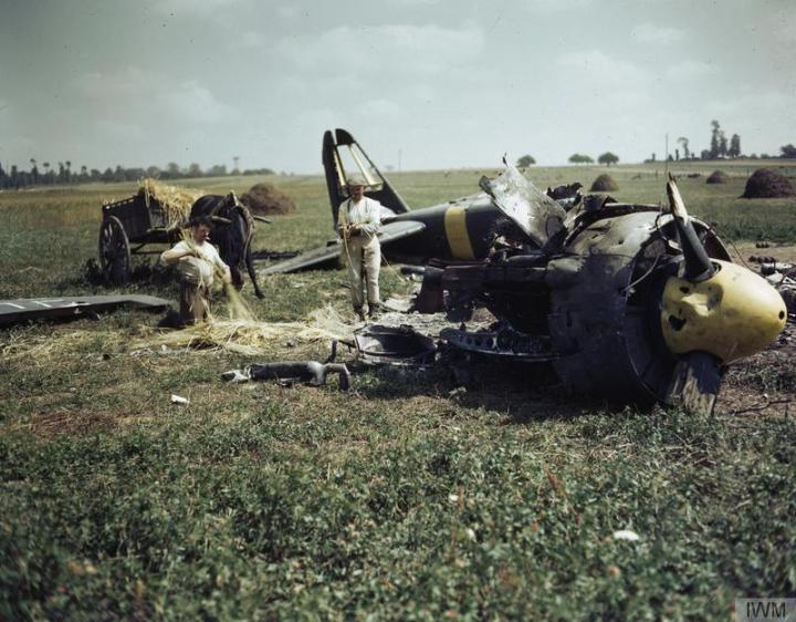 Two French farmers work around the wreckage of a Luftwaffe Ju-88 in Normandy, 1944. (IWM TR 2107)