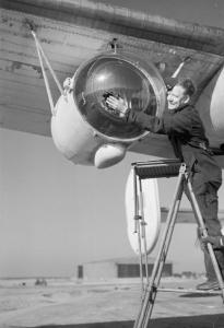 Ground crew polish the cover of a 22 million candela Leigh Light, fitted to a Coastal Command Liberator GR.V. (IWM CH 13997)