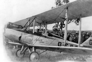 Bert Hinkler runs the engine of his Avian G-EBOV for a crowd of onlookers, somewhere in Queensland after his 1928 flight from England. (State Lib. of Queensland)
