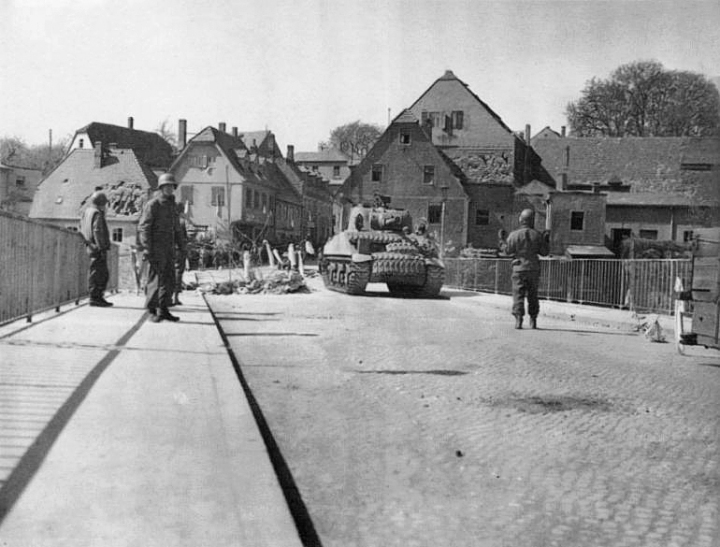 US soldiers on Colditz Bridge, April 16th, 1945. Damage to the town is evident, and the barricade on the right of the bridge marks damage to the centre piling. (wikipedia)