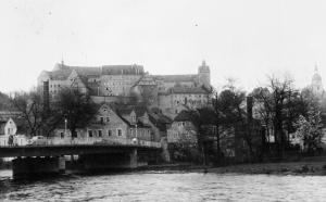 Colditz Castle from the opposite bank of the Mulde River, with the town's road bridge in the foreground. (IWM)