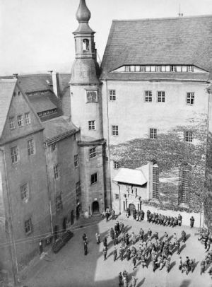 Prisoners parade in front of the French quarters, Colditz. The Glider was built in the upper attic (above the windows) of this building, and launched along the roofline behind the tower at centre-left.