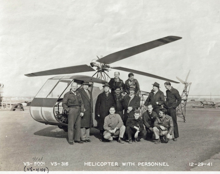 "The Sikorsky team that prepared the R-4, gathered at Stratford, CT at the end of 1941. BACK: Edward Ortlepp; and Adolph Plenefisch, Shop Foreman. STANDING: Alex Krapish, Michael Buivid, Supervisor Vought-Sikorsky Test Lab; Igor. Sikorsky; Fritz Papini, Bob Labensky, XR-4 Project Engineer; Walter Stens, and Henry Wirkus. FRONT: Robert Kretvix; George ""Red"" Lubben, Mechanic; Miles ""Bud"" Roosevelt, Mechanic; and Ed Walsh, Crew Chief. (© 2016 Igor I. Sikorsky Historical Archives, Inc.)"