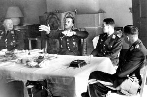 Ever the fighter pilot, (then Oberstleutnant) 'Dolfo' Galland (hands raised), talks with Werner Molders and Theo Osterkamp (to his left, respectively) at the latter's birthday in April 1941. (Bundesarchiv, Bild 183-B12018 / CC-BY-SA 3.0, via wikipedia)