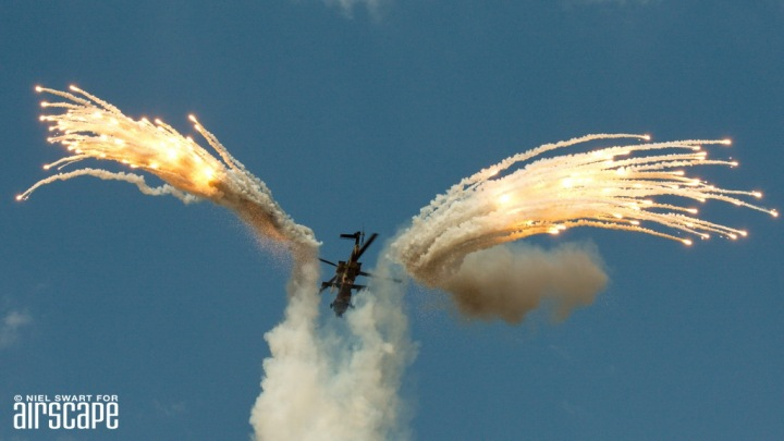 A Denel Rooivalk attack helicopter (cn 681) of SAAF 16 Squadron fires off flares. Based on the Aerospatiale Puma and heading into a major upgrade program, the Rooivalk (Red Falcon) is an ongoing South African success. (© Niel Swart)