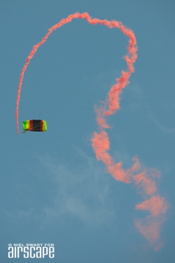 Leaving a stream of orange smoke, a SAAF skydiver opens the air show at AAD2016. (© Niel Swart)